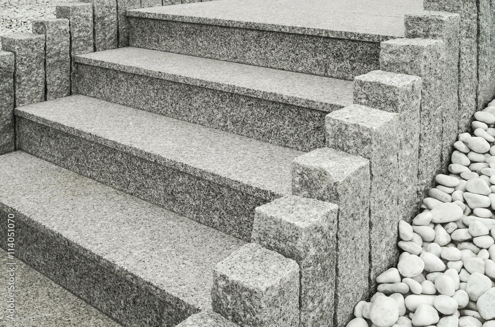 Fototapeta Closeup einer modernen Außentreppe aus Granit mit Stelen und Drainage aus großen weißen Kieselsteinen - Closeup of a modern exterior granite staircase with palisades and drainage of pebbles