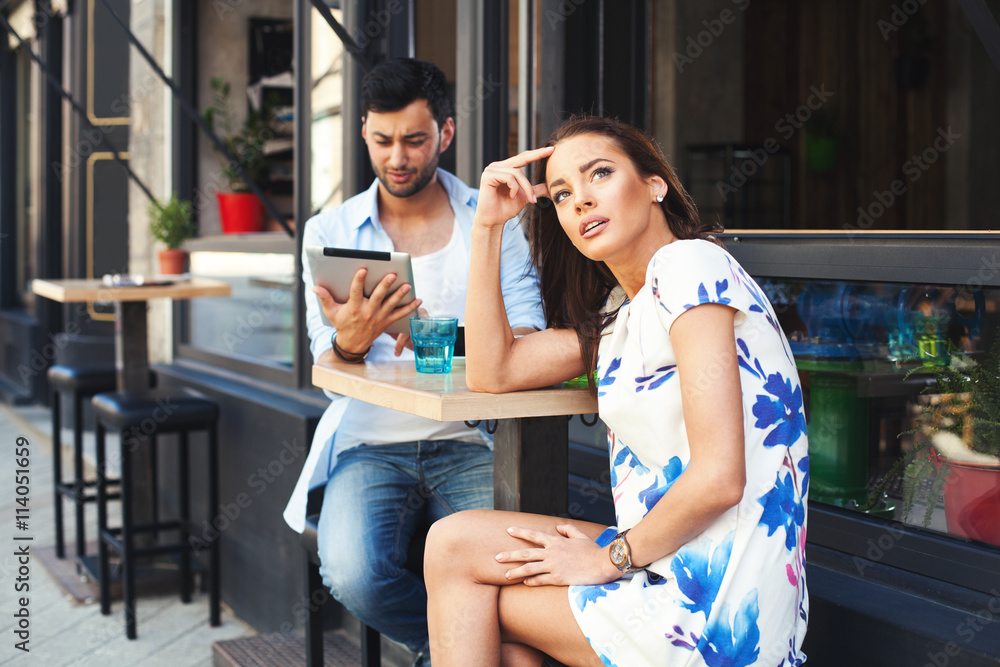 Fototapety, obrazy: Bad date.  Man having fun with digital tablet during a date with