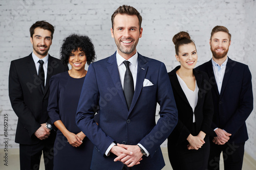 Fototapeta Group of businesspeople standing as a team with happy teamleader obraz