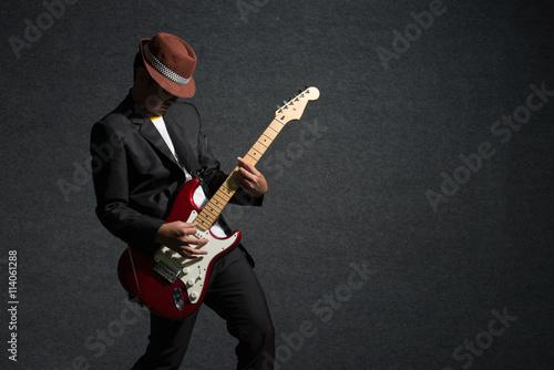 Fototapeta music concept, guitarist in dark