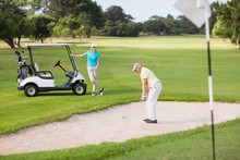 Golfer Playing On Sand Trap By Woman
