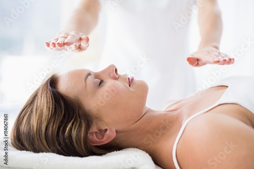 Midsection of therapist performing reiki treatment on woman Canvas Print