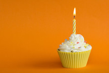 Yellow Cupcake With Candle And Orange Background