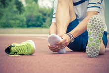 Jogger Hands On Foot. He Is Feeling Pain As His Ankle Or Foot Is Broken Or Twisted. Accident On Running Track During The Morning Exercise. Sport Accident And Foot Sprain Concepts.