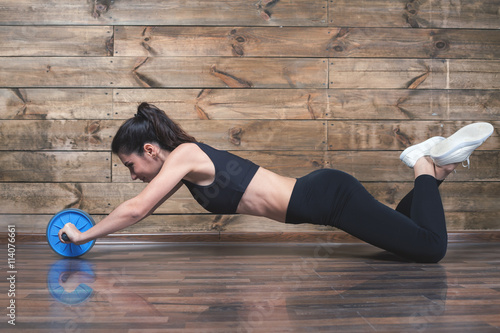 plakat Attractive woman with slim stomach do abdominal exercises with wheel