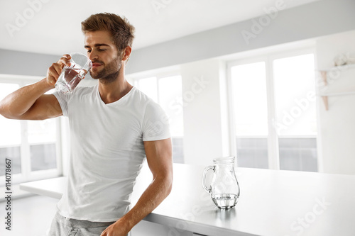 Fotografie, Obraz  Handsome Man Drinking Glass Of Fresh Water Indoors In Morning