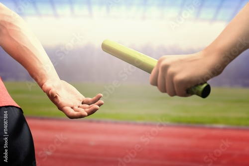 Fotografia  Composite image of athlete passing a baton to the partner