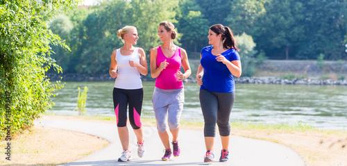 Fotografie, Obraz  Gruppe von Frauen beim Laufen am Flussufer