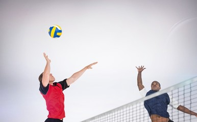 FototapetaComposite image of sportsman posing while playing volleyball
