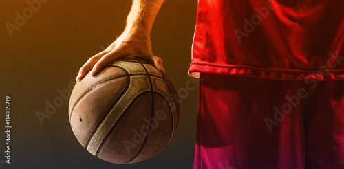 Photo  Close up on a basketball held by basketball player