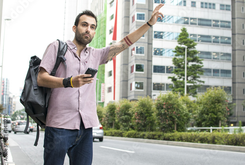 Billede på lærred Young White Man With Cellphone Hailing Uber Taxi