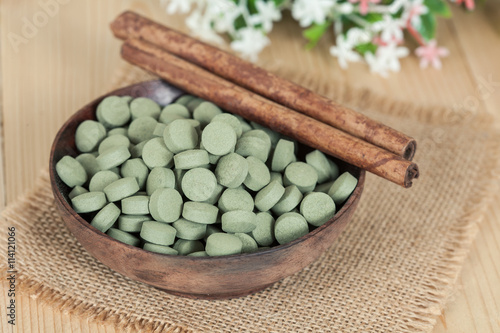 plakat Herbal pill on wooden bowl. herb for healthy living.