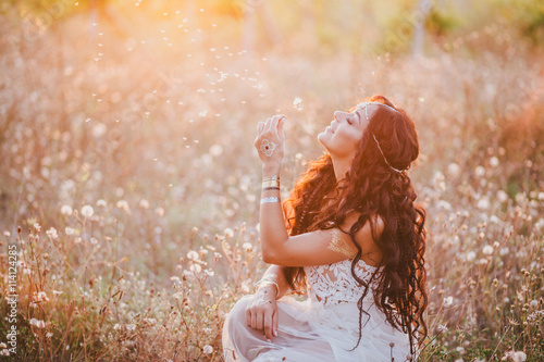 Photo  Beautiful young woman with long curly hair dressed in boho style dress posing in a field with dandelions