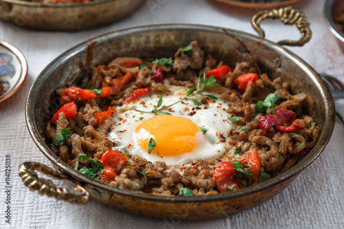 Fried egg with mince meat in traditional turkish pan
