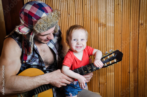 Little kid baby with his hipster father playing guitar on