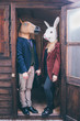 Couple of young beautiful millennial woman and man wearing horse and rabbit mask standing on the front door of a wooden house - carnival, strange concept