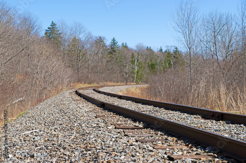 Railroad Railroad tracks leading to bend with forest and blue sky above.