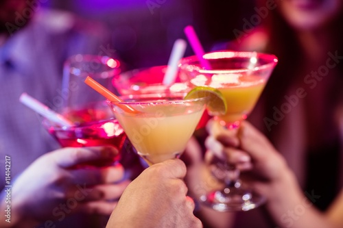 Group of friends toasting cocktail at bar counter
