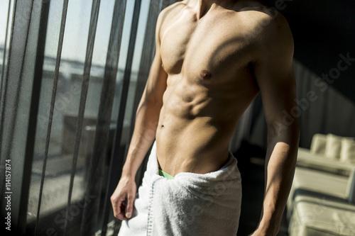 Fototapeta Man with a towel in a room obraz na płótnie