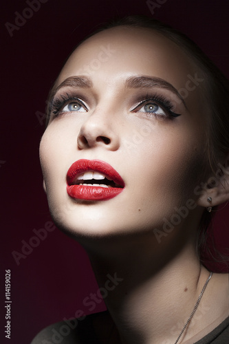 Fototapeta Beautiful girl with red lips and blue eyes looking up with open mouth obraz na płótnie