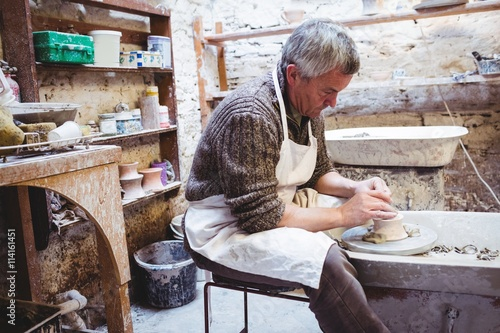 Side view of craftsman in pottery workshop