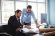Businessmen working on blueprint in office