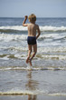Child blond boy playing on sandy beach, summer time
