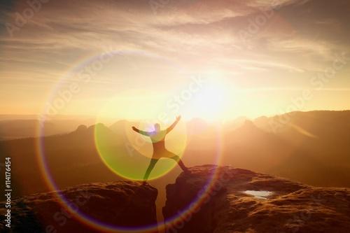 Jumping hiker celebrate triumph on cliff Fototapeta