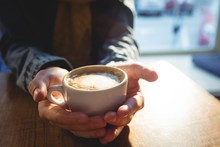 Close-up Of Woman Holding Coffee Cup At Cafeteria