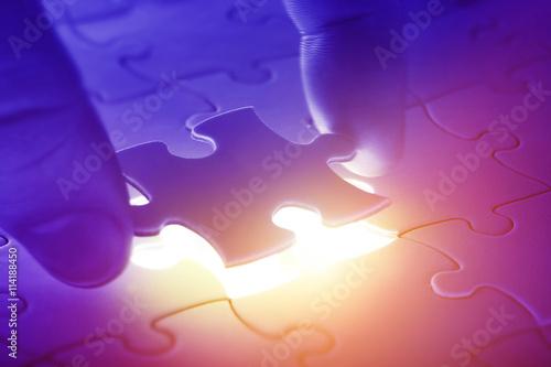Photo  Hands placing last piece of a Puzzle
