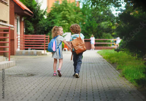 Fotografía  El muchacho y la Gerlie van a la escuela tienen manos unidas.
