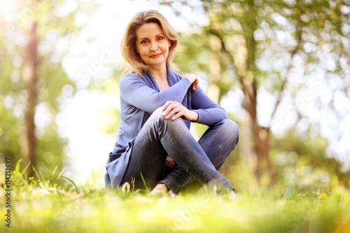 Fotografía  Frau im besten Alter sitzt in der Natur
