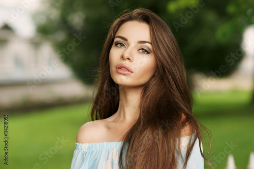 Fototapety, obrazy: Young beautiful woman with long brunette hair. Calm girl with perfect clean skin posing in park and looking in camera