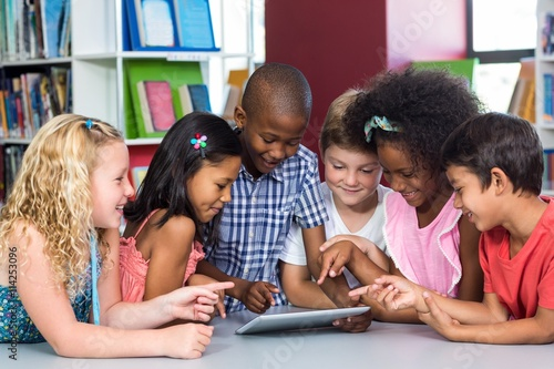 Mixed race children using digital table in library