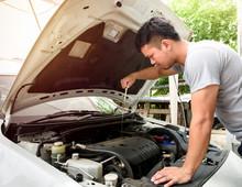 A Man Checking Car Engine At Home