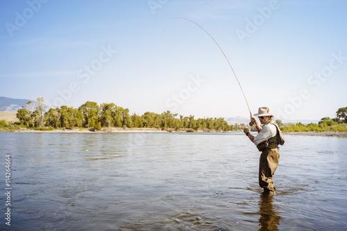 Poster Peche Man wearing waders fishing in river