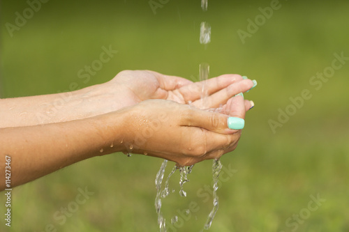 Poster Natuur A stream of fresh clean water flowing to the hands of a girl with beautiful manicure