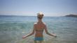 Sexy back of a beautiful woman on tropical beach in blue bikini