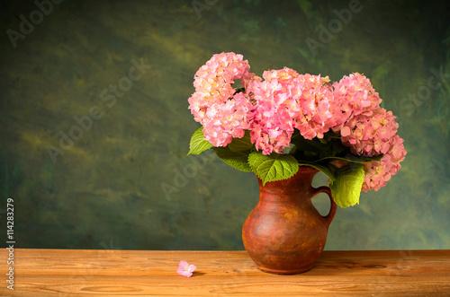 Fotografie, Obraz  Pink hydrangea in a ceramic vase on the voden table