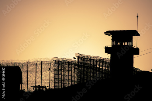 Silhouette of barbed wires and watchtower of prison in Neapolis, Crete, at sunse Canvas-taulu