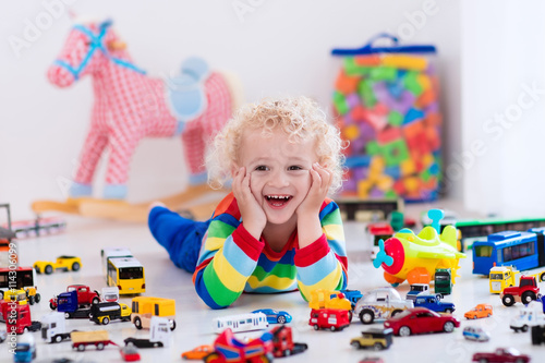 obraz lub plakat Little boy playing with toy cars