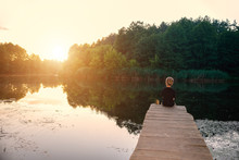 A Boy Sits On A Wooden Bridge On The River In A Picturesque Setting At Sunset. Toning