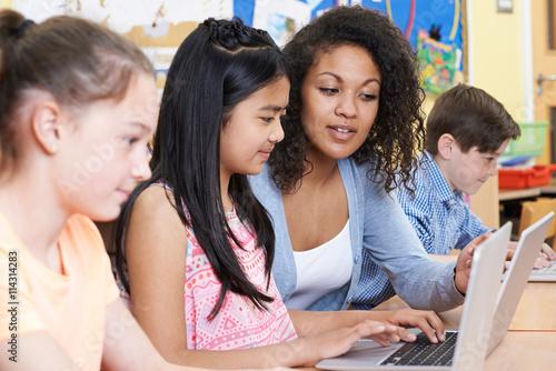 Valokuvatapetti Teacher Helping Group Of Elementary School Children In Computer