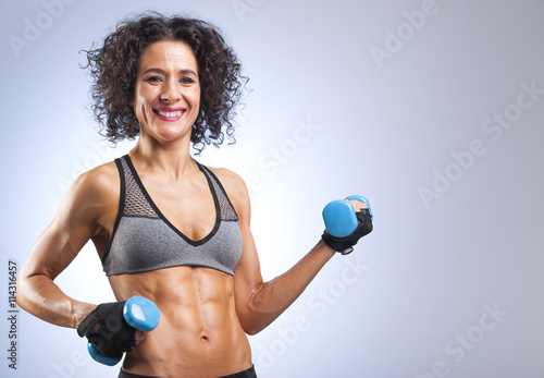 plakat Fit woman lifting weights on gray bakground