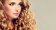 Leinwanddruck Bild - Beautiful girl with long wavy hair . Blonde model with curly hairstyle .