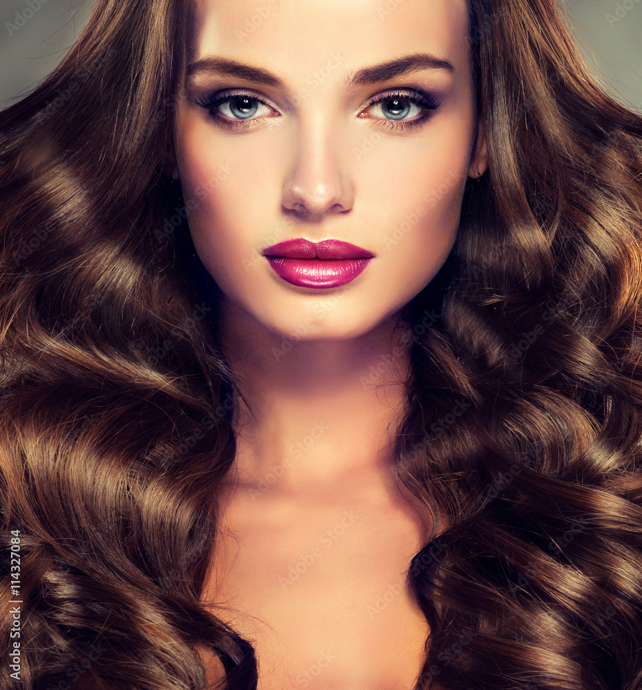 Beautiful girl brunette  hair with an elegant hairstyle , hair wave ,curly hairstyle . Fashion make up .