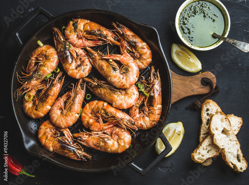 Roasted tiger prawns in iron grilling pan with fresh leek, lemon, bread and pest Canvas Print