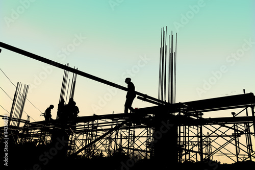 Stampa su Tela Silhouette of construction workers working on scaffolding at a h