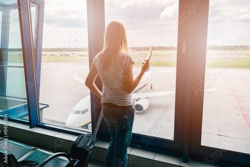 Fotografie, Obraz  Žena dělá rezervaci na let s telefonem