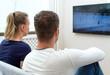 Couple watching hockey match on tv.